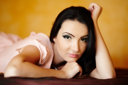 Closeup portrait of a young woman lying on the bed in her bedroom, with selective focus Stock Photo - 20245002