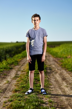 Outdoor portrait of a teenager boy standing in the middle of a rural dirt road Stock Photo - 20244994