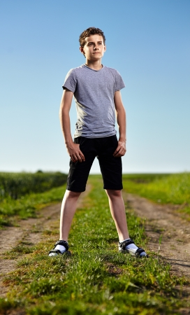 Outdoor portrait of a teenager boy standing in the middle of a rural dirt road Stock Photo - 20245048