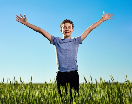 Portrait of a teenage boy in a green wheat field at sunset against clear blue sky Stock Photo - 20245438
