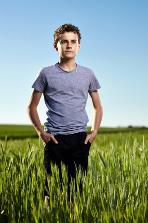 Portrait of a teenage boy in a green wheat field at sunset against clear blue sky Stock Photo - 20245025