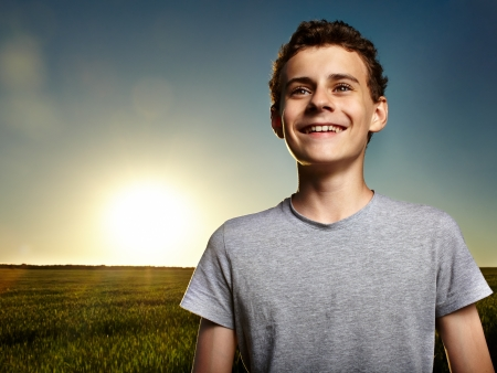 Closeup of a teenage boy with the sun behind him at sunset, in a wheat field photo