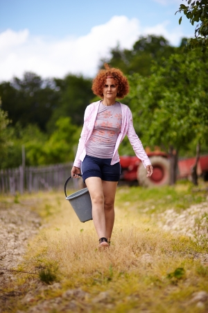 Farmer woman carrying a bucket with fertilizer in an orchard, with selective focus Stock Photo - 20245005