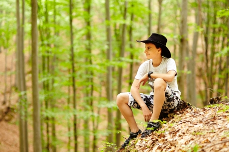 Portrait of a teenage boy in shorts and t-shirt in a forest, relaxing Stock Photo - 20244995