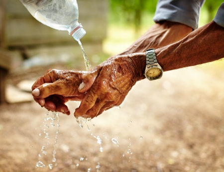 poor people: Old man washing his hands with water pouring from a plastic bottle