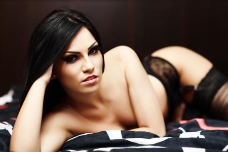 the naked girl: Primer retrato de una joven mujer en topless en ropa interior acostada en la cama Foto de archivo