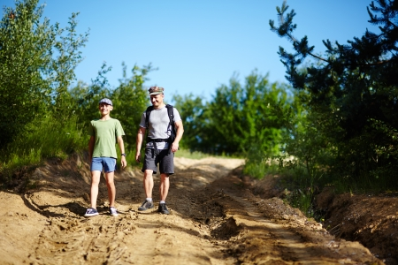 Father and son trekking in a rural landscape with dirt road photo
