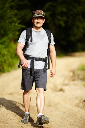 Man with backpack trekking in a rural area with forest and dirt road, full length photo