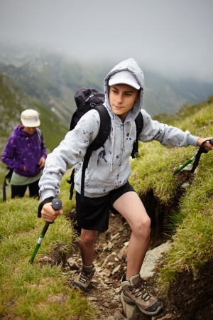 Teenage boy and his mother hiking into the Romanian Carpathians mountains photo