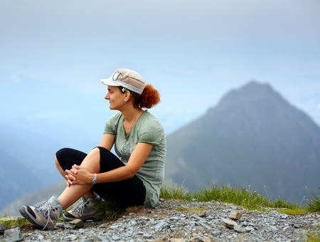 Caucasian woman with cap sitting on a mountain with a peak in background photo