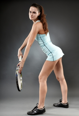 A full length studio shot of a female tennis player standing ready to serve photo