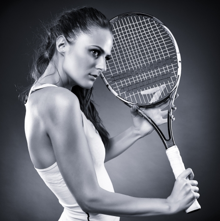 A monochrome studio shot of a young female tennis player holding the racket photo