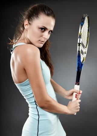 backhand: Un estudio de disparo de un jugador de tenis femenino joven dando un golpe de rev�s Foto de archivo