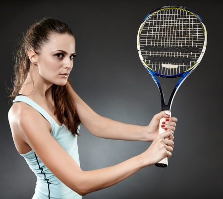 backhand: Studio shot of a young woman executing a backhand volley