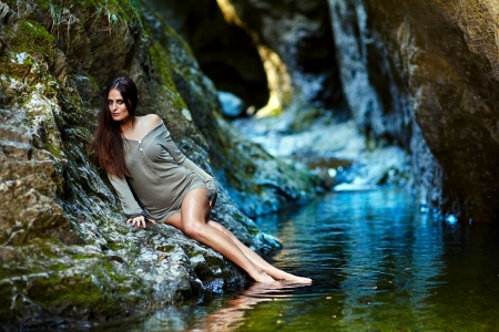 Portrait of a young sexy woman leaning on the rock close to a mountain waterfall photo