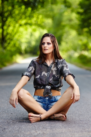 Beautiful young woman sitting on the road and looking ahead  photo