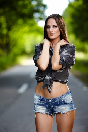 Poertrait of a sexy young woman standing on the road  photo
