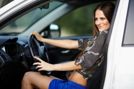 Portrait of sexy girl sitting in a car with the hands on the wheel photo