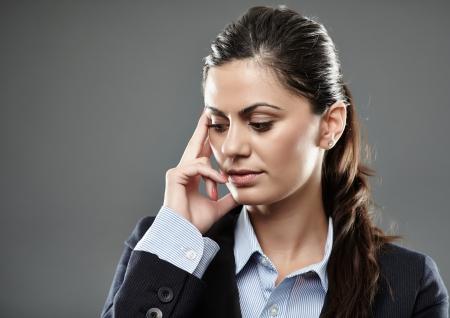 Studio shot of pensive businesswoman with hand on head photo
