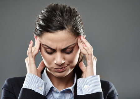 Businesswoman with strong migraine over gray background Stock Photo