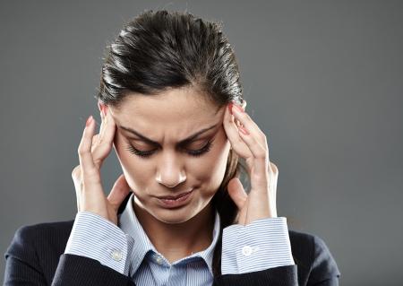 Femme d'affaires avec une forte migraine sur fond gris Banque d'images - 22355815