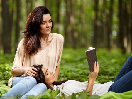Mother and daughter sitting in the forest on a blanket with daughter resting her head on her mothers knees reading together from a book photo
