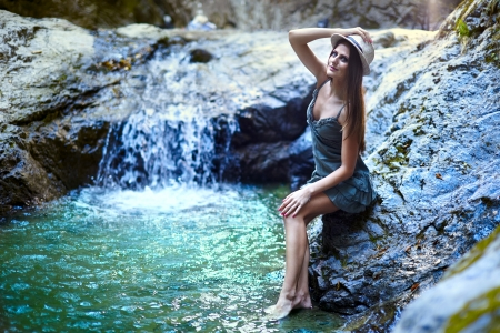 Attractive young woman sitting near a waterfall photo