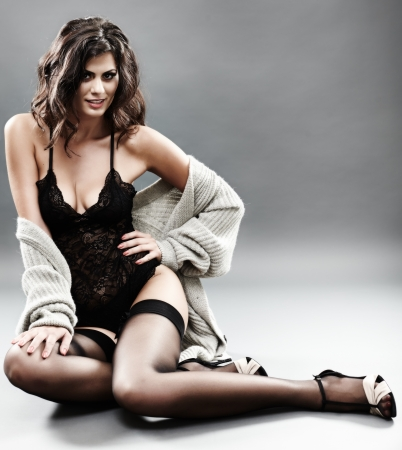 Studio portrait of a sexy brunette in black lingerie, stockings and cardigan over grey background photo