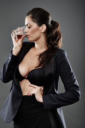 Sexy businesswoman in bra and suit drinking a glass of brandy photo