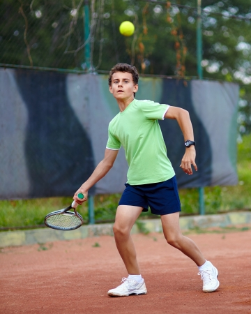 Child hitting the ball with the forehand on a dross court photo