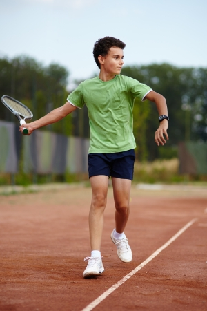 dross: Child hitting the ball with the forehand on a dross court