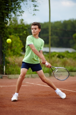 Child hitting the ball with the backhand on a dross court Standard-Bild