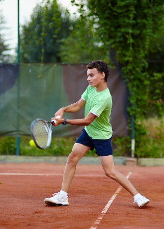 dross: Child hitting the ball with the backhand on a dross court Stock Photo