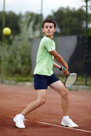 slag: Child hitting the ball with the backhand on a dross court Stock Photo