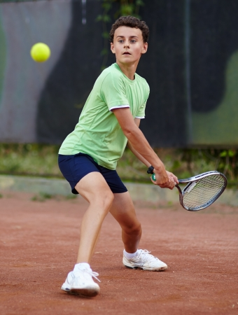 Child hitting the ball with the backhand on a dross court photo