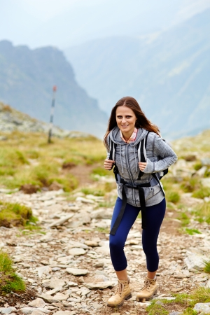Woman hiker with backpack on a mountain trail photo