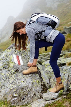 Woman hiker with backpack on a mountain trail tying the shoelaces photo