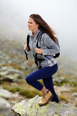 mountain climbing: Woman hiker with backpack climbing on the mountain over a misty background Stock Photo