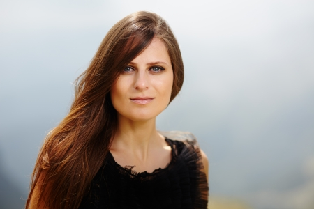 Closeup of an attractive woman on a mountain lanscape photo