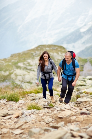 Portrait of a couple holding hands and talking on a mountain trail photo
