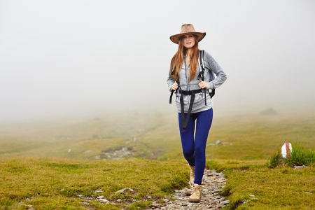 Female hiker with backpack and hat on a mountain trail photo