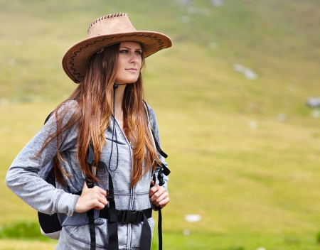 Female hiker with backpack and hat looking ahead photo