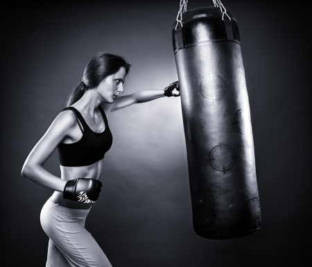 Monochrome portrait of young woman hitting the punching bag photo