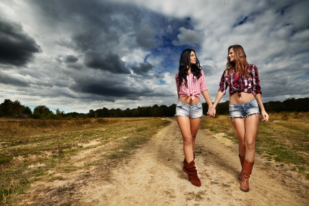 Portrait of two female farmers walking hand in hand in the countryside photo