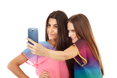 Portrait of two friends taking photos of themselves with a cell phone isolated on white photo