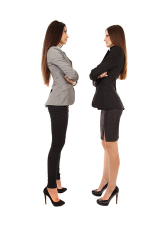 Portrait of two young successful businesswomen isolated on white background