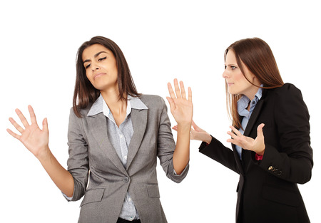 Portrait of two businesswomen having an argument isolated on white background Foto de archivo