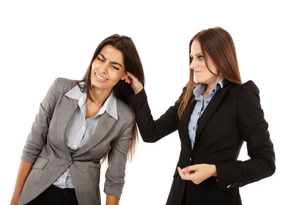punishments: Portrait of businesswoman pulling colleagues ear isolated on white Stock Photo