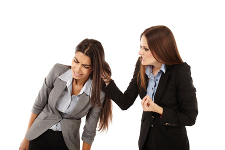 Portrait of businesswoman pulling colleagues ear isolated on white photo