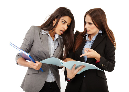 Two successful businesswomen dicussing and looking to documents isolated on white photo